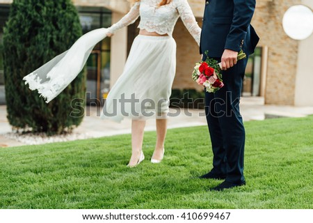 bride and groom is running with joined hands on a city park road sunshine
