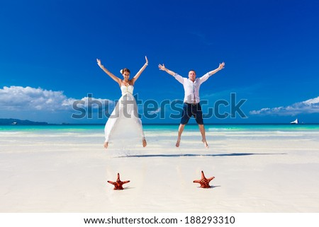 Bride and Groom jumping on tropical beach shore with two red starfish in the sand - stock photo
