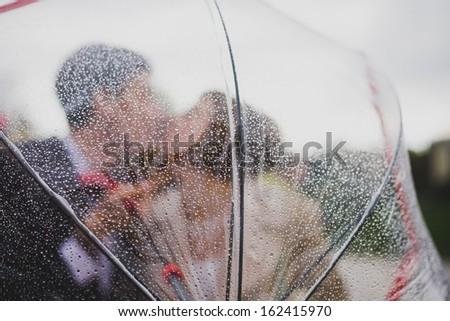 bride and groom kiss, blocking umbrella - stock photo