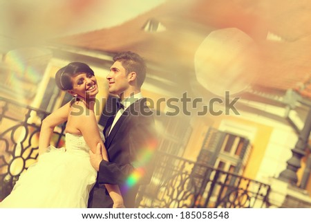 Bride and groom kissing and embracing in the city - stock photo