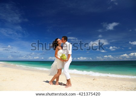Bride and groom kissing and having fun at sandy tropical beach