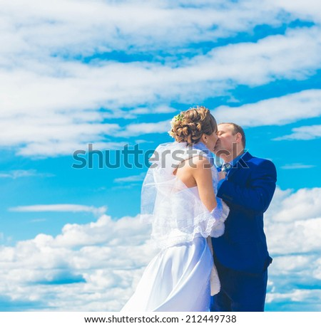 bride and groom kissing and hold