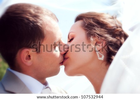 Bride and groom kissing close-up