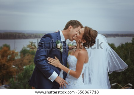 bride and groom kissing on a background of the river.
