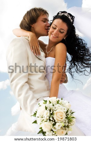 Bride and groom kissing on the blue sky background - stock photo