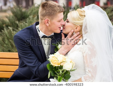 bride and groom kissing while sitting on a bench