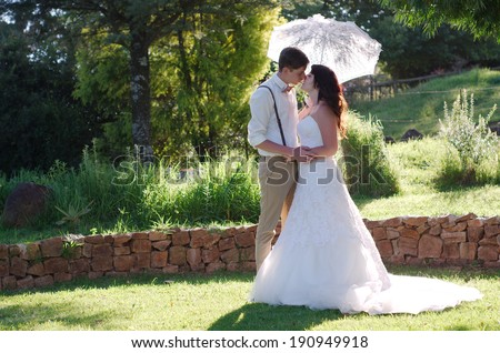 Bride and groom kissing with parasol in outside garden wedding ceremony - stock photo
