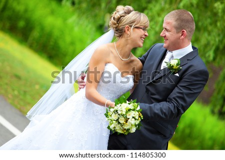 BRIDE AND GROOM LAUGHING and looking to each other while holding the yellow roses bouquet - stock photo