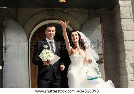 Bride and groom leaving the church after a wedding ceremony - stock photo