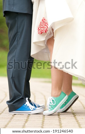 Bride and groom' legs in color gym shoes, with red-white lollipop - stock photo