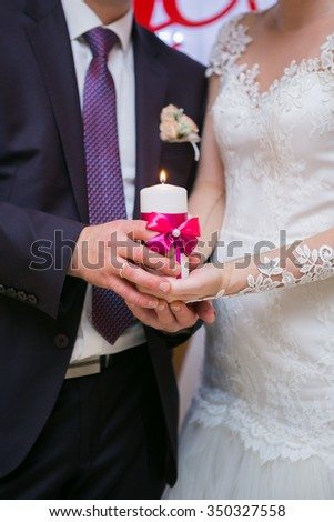 bride and groom lighting candle close up - stock photo