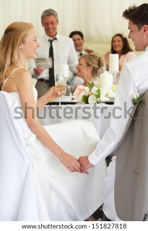 Bride And Groom Listening To Speeches At Reception - stock photo