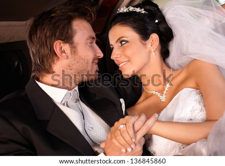 Bride and groom looking fondly of each other. - stock photo