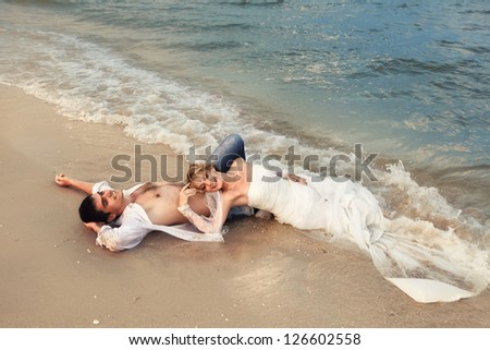 Bride and Groom lying in beach shore