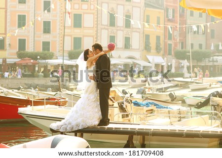 Bride and groom near port with cityscape - stock photo