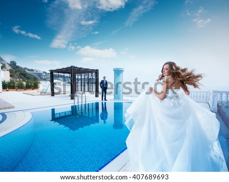 Bride and groom near the swimming pool. Honeymoon wedding the young couple. The woman in a beautiful dress runs to the man in the suit. Luxury resort.