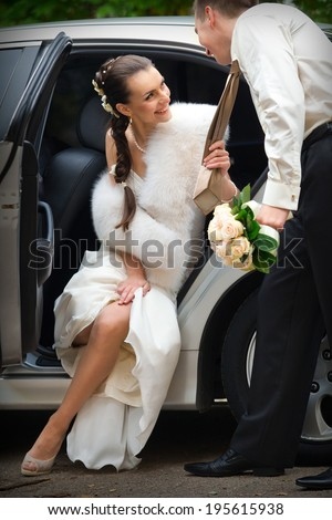 Bride and groom next to wedding car - stock photo
