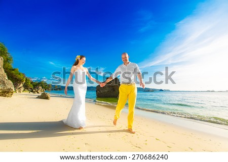 bride and groom on a tropical beach with the sunset in the background - stock photo