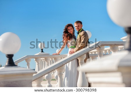 Bride and groom on a white ladder with handrail