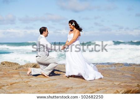bride and groom on beach rocks - stock photo