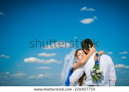 bride and groom on the background of blue sky. Happy couple. Newlyweds embracing. Wedding bouquet in a hand.