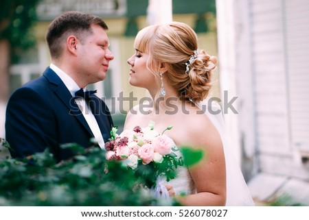 bride and groom on the background of the garden fence.