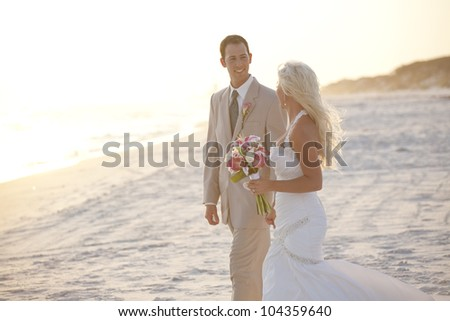 Bride and Groom on the Beach at Sunset - stock photo
