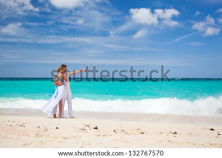 Bride and groom on tropical beach, walking - stock photo