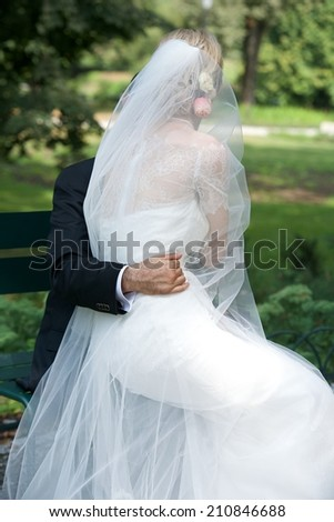 Bride and groom on wedding day, unknown unrecognizable couple on wedding day sitting in the park, romantic mood  - stock photo