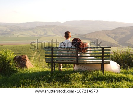 Bride and groom outside garden wedding on bench with African Natal Midlands mountain scenery background