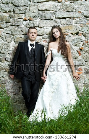 Bride and groom over stone brick wall outdoors