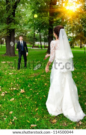 bride and groom playing badminton in the park