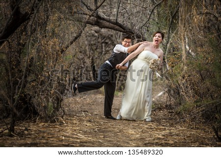 Bride and groom playing together in forest - stock photo