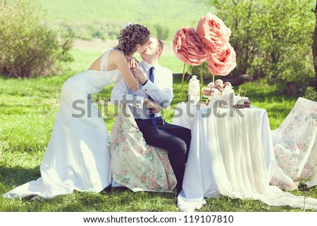 Bride and groom posing at the decorated banquet table in the park in the summer. Enjoy a moment of happiness and love. A series of photos in my portfolio. - stock photo