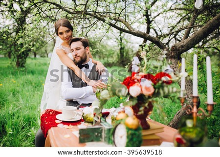 Bride and groom posing at the decorated banquet table in the park in the summer. Enjoy a moment of happiness and love. A series of photos in my portfolio. Groom with beard