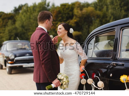Bride and groom posing by a vintage car