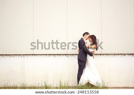 Bride and groom posing outdoors - stock photo
