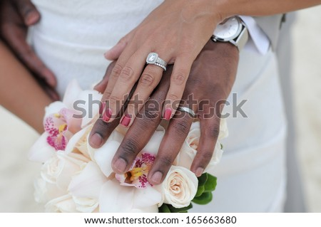 Bride and groom put their hands together and show the rings - stock photo