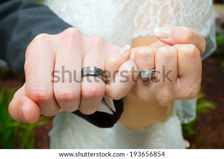 Bride and groom put their hands together in the pinky swear position to show off their wedding rings after the ceremony. - stock photo