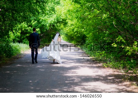 bride and groom running down the alley - stock photo