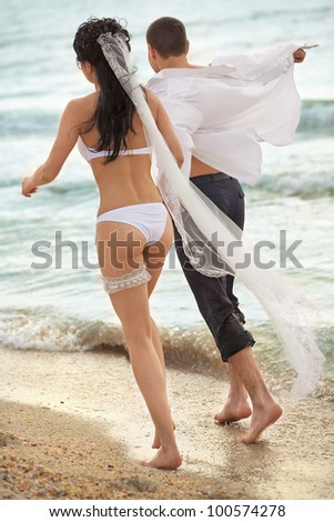 Bride and groom running in sunshine on a beautiful tropical beach - stock photo