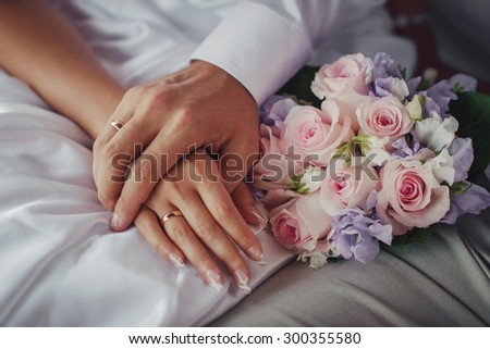 bride and groom's arms with rings and a wedding bouquet - stock photo
