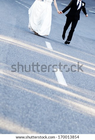 bride and groom's feet running