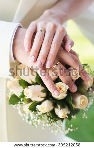 Bride and groom's hands with wedding rings on the bouquet with white roses - stock photo