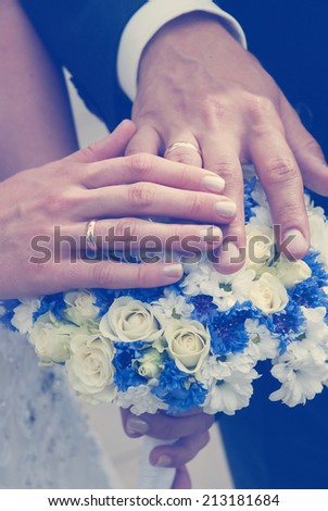 Bride and groom's hands with wedding rings on the wedding bouquet. Close-up image. - stock photo