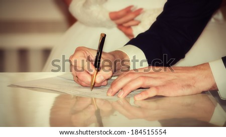 Bride and Groom Signing Marriage Certificate - stock photo