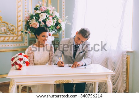Bride and groom signing marriage license or wedding contract
