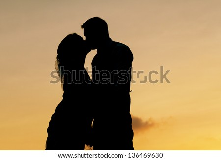 bride and groom silhouette kissing . - stock photo