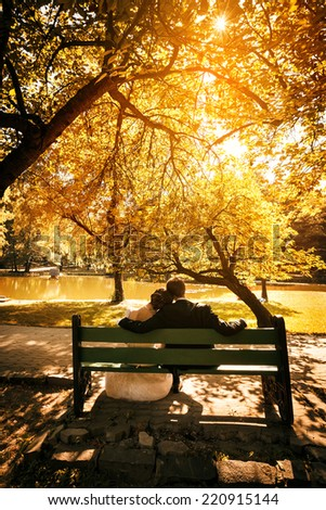 Bride and groom sit on bench in park in sunset light - stock photo