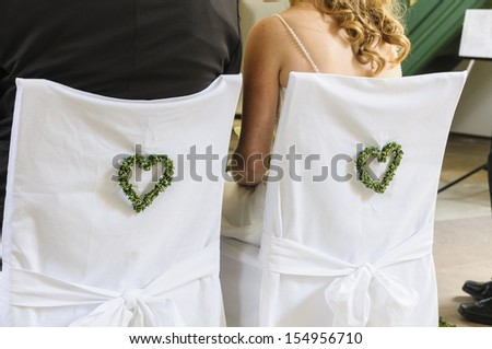 Bride and groom sitting in front of the altar during the church ceremony, you can see the two from behind. The two chairs are covered with slipcovers and decorated with hearts. - stock photo